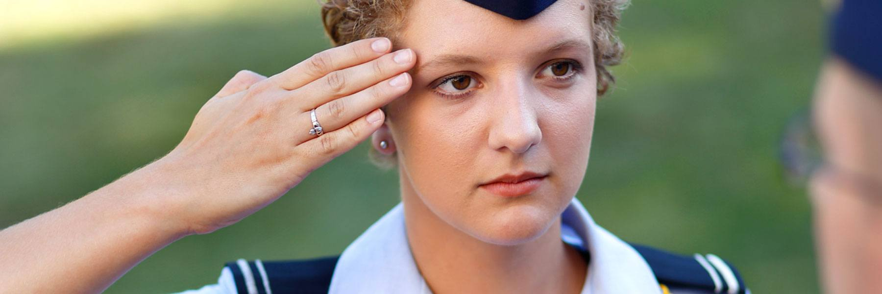 Female cadet wearing Air Force blues salutes a cadre member.