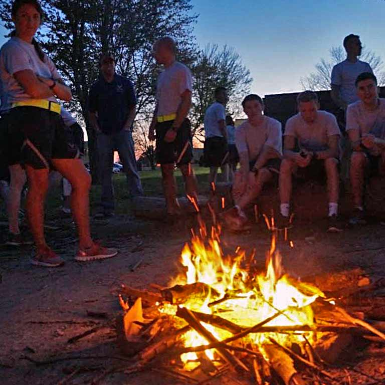 Cadets sit around an evening campfire.