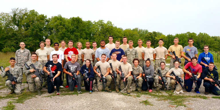 A group of cadets pose with rifles at a shooting range.