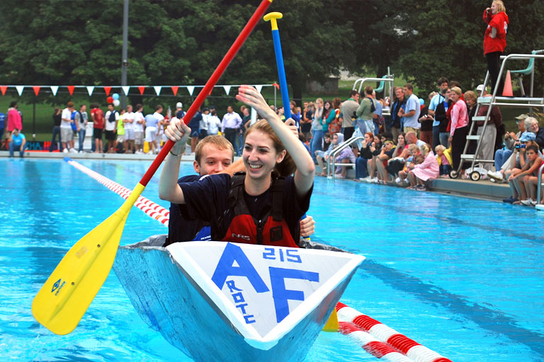 Two cadets in a makeshift boat race in an outdoor pool regatta competition.