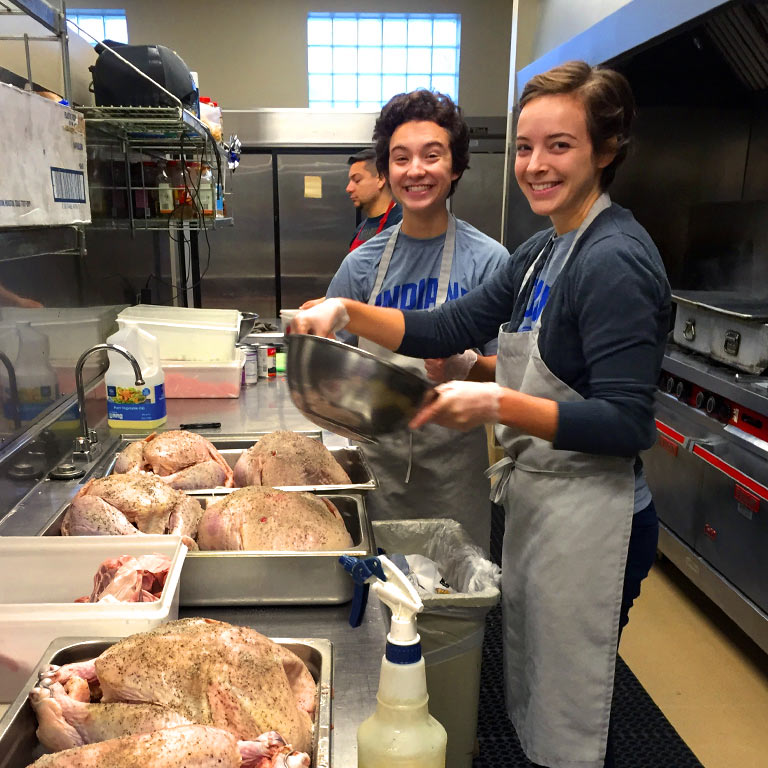 Student volunteers cook in a community kitchen.