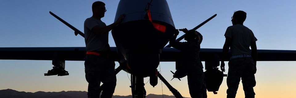 The silhouettes of two airmen with a fighter jet on a tarmac at sunrise