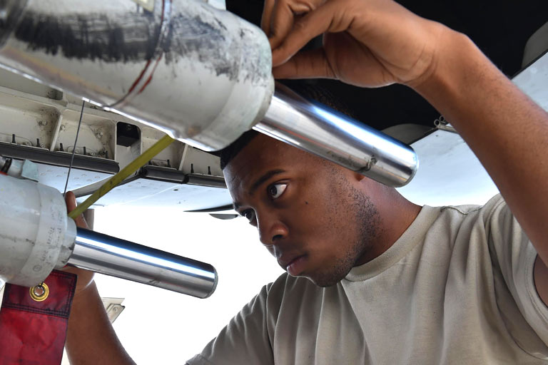 A young Air Force mechanic works on the engine of a plane.