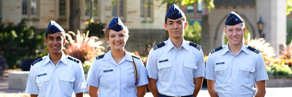 Four Air Force ROTC cadets stand in uniform in front of the Sample Gates at IU Bloomington.