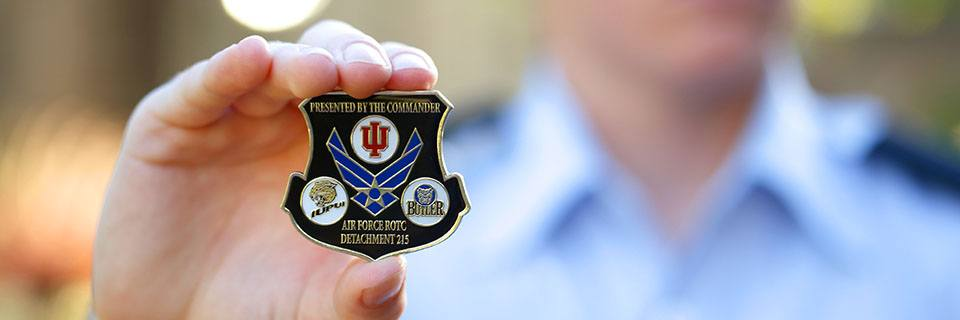 Cadet holding the Air Force ROTC Detachment 215 coin